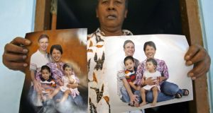 Widi Yuliono  shows photographs of his relativesJohn Paulisen (Top-L), Yuli Hastini (Top-R), Arjuna Martin Paulisen (L) and Sri Paulisen (R) who are victims of the Malaysian Airline flight MH 17 plane disaster in eastern Ukraine, at his home  in Solo, Central Java, Indonesia. Photograph: Mohammad Ali/EPA