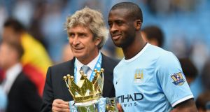 Manchester City manager Manuel Pellegrini and Yaya Toure pose with the Premier League trophy at the end of the season. Photograph: Getty Images