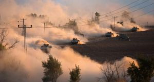 Israeli tanks manoeuvre outside the northern Gaza Strip amid clouds of dust today. Photograph: Ronen Zvulun/Reuters