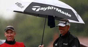 Darren Clarke taks shelter from the rain at the start of his round on day three of the British Open. Photo: David Davies/PA Wire.