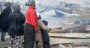 People watch as their dwellings are dismantled in Lwandle, an impoverished area about 45km from Cape Town, after the South African National Roads Agency Limited obtained a court order to  remove squatters from the land. Photograph:  Rodger Bosch/AFP/Getty Images