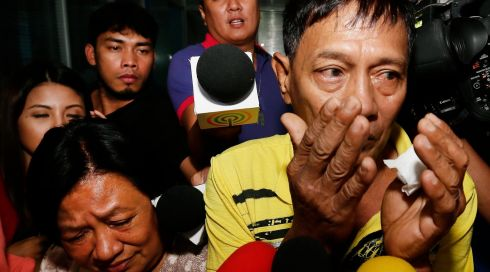 Linda (L) and Tirso Pabellon (R) - siblings of Irene Pabellon Gunawan, one of the three Filipinos who are victims of the Malaysia Airline disaster in eastern Ukraine - walk in tears  after securing their passports at the Department of Foreign Affairs in Manila, Philippines. Photograph:  EPA/DENNIS M. SABANGAN