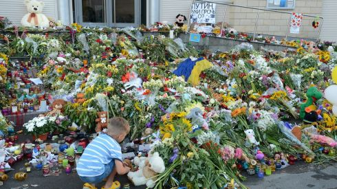 A young boy lays a teddy bear at a floral tribute to the crash victims outside the Dutch embassy in Kiev, Ukraine. Photograph: EPA/DAVE HUNT
