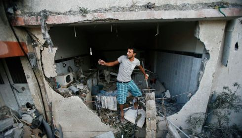 A Palestinian man inspects a house that police said was damaged in an Israeli air strike. Photograph:  REUTERS/Suhaib Salem