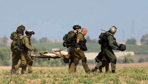 A wounded Israeli soldier is carried on a stretcher to a helicopter for evacuation outside Gaza. Photograph: REUTERS/Ronen Zvulun