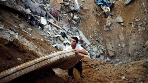 A Palestinian salvages a mattress from the remains of a house in Khan Younis. Photograph: REUTERS/Ibraheem Abu Mustafa