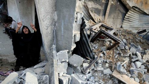 A Palestinian woman reacts next to the rubble of her relatives' house. Photograph: REUTERS/Ibraheem Abu Mustafa