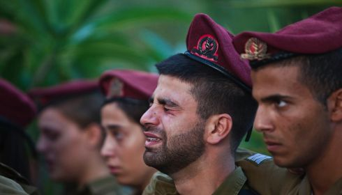 Israeli soldiers mourn during the funeral of Bnaya Rubel in Holon, near Tel Aviv. Eighteen Israeli soldiers, including Rubel, and two Israeli civilians have been killed since the Gaza offensive was launched in response, Israel says, to mounting cross-border rocket attacks by Hamas militants. Photograph: REUTERS/Nir Elias