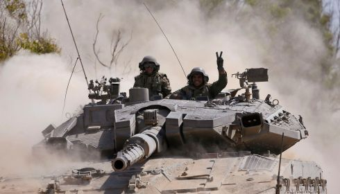 An Israeli soldier gestures from a tank near the border with Gaza. Photograph: REUTERS/Baz Ratner