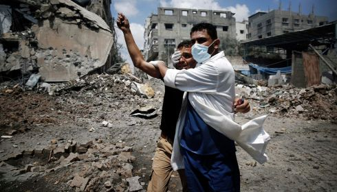 A medic helps a Palestinian in the Shejaia neighbourhood, which was heavily shelled by Israel. Photograph: REUTERS/Finbarr O'Reilly