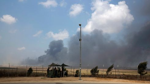 Smoke rises as Israeli soldiers stand near the border with Gaza. At least 40 Palestinians were killed on Sunday, July 20th, by Israeli shelling, health officials said. Photograph: REUTERS/Baz Ratner