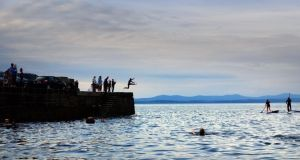 Families enjoy the long evening light at dusk as they watch people jump from Creevy Pier, kayak and paddle board in Donegal Bay last week.  Photograph: Bryan O'Brien/The Irish Times