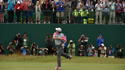 Rory McIlroy throws his ball to spectators as he celebrates on the 18th green. Photograph: REUTERS/Toby Melville