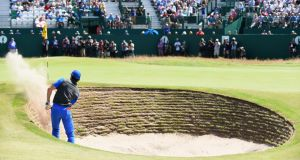 Rory McIlroy plays a bunker shot on the 18th hole during the first round. Photograph: Stuart Franklin/Getty Images