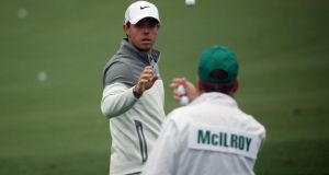 Rory McIlroy of Northern Ireland catches a golf ball from caddie JP Fitzgerald during a practice round prior to the start of the 2014 Masters Tournament at Augusta National Golf Club. Photograph: Andrew Redington/Getty Images