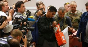 A Malaysian expert (C) examines a black box belonging to Malaysia Airlines flight MH17 during its handover from pro-Russian separatists, in Donetsk.