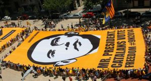 Demonstrators with the pro-independence Catalan National Assembly hold a giant banner with an image of US president Barack Obama at Plana square in Badalona, near Barcelona. Photograph: Gustau Nacarino/Reuters
