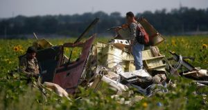 A Malaysian air crash investigator (R) inspects the crash site of Malaysia Airlines Flight MH17, near the village of Rozsypne, Donetsk . Photograph: Maxim Zmeyev /Reuters