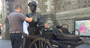 The Molly Malone statue being cleaned by a member of Dublin City Council. Photograph: Eric Luke