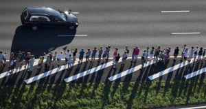 Mourners line the route as hearses carrying bodies of the victims of the MH17 plane crash drive in a convoy from the airbase in Eindhoven to Hilversum in The Netherlands today.  Photograph: Jerry Lampen/EPA
