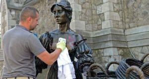 Dab hand: cleaning the graffiti off Molly Malone this week. Photograph: Eric Luke