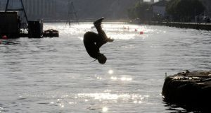 A local teenager enoying the hot weather dives into the Grand Canal Basin in Dublin yesterday. Photograph: The Irish Times