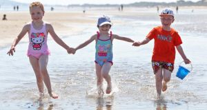 (From left) Lacey Turner (5), Holly McCartin (5) and Jack Turner (5) from Portmarnock and Coolock enjoying the soaring temperatures at Portmarnock Beach in Dublin. Photograph: Collins