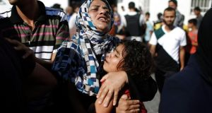 A Palestinian mother comforts her child after what medics said was an Israeli shell that hit a UN-run school sheltering Palestinian refugees, at a hospital in Jabaliya in the northern Gaza Strip. Photograph: Finbarr O'Reilly/Reuters