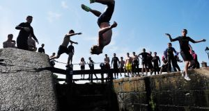 Head first: jumping into the Grand Canal at Suir Road Bridge in Drimnagh, Dublin, yesterday. Photograph: Aidan Crawley