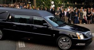 People watch as a convoy of hearses arrives at the Korporaal van Oudheusdenkazerne in Hilversum. Photograph: EPA
