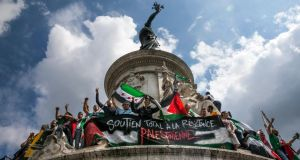 Protesters stand on the Statue de la Republique holding a poster in French reading 'Total support for the Palestinian Resistance' during a protest in support of Palestinians in Gaza, at Paris in France today. Photograph: Etienne Laurent/EPA