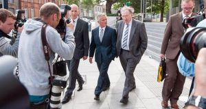 Former  junior minister of State Ivor Calley (centre) with members of his legal team outside Dublin Circuit Court yesterday.   Photograph: Collins Courts