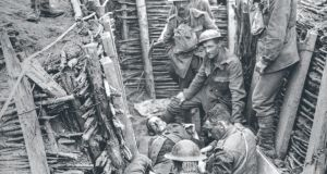 Irish Guards with a wounded man in a trench in Wytschaete, Belgium. Photograph: Fr Browne.