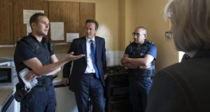 Britain's prime minster, David Cameron, and home secretary Theresa May speak to Home Office immigration enforcement officers at a property in Slough where six immigrants were arrested yesterday. Photogrpah: Oli Scarff/Getty Images