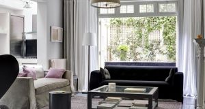 A bronze floor lamp and square coffee table are key components of the sitting room. Photograph: Luke White