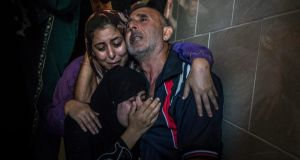 Members of the Abid Raboh family mourn the death of a child who was reportedly killed by shelling, during funerals in Jabaliya near Gaza City yesterday. Photograph: Sergey Ponomarev/The New York Times