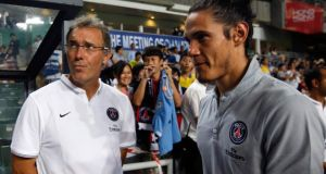 Paris Saint-Germain player Edinson Cavani (right) walks past head coach Laurent Blanc before their friendly match against local team Kitchee in Hong Kong. Photograph: Tyrone Siu/Reuters