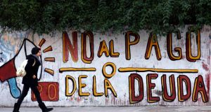 "A woman walks past a graffiti that reads ""No to the debt payment"" in Buenos Aires. Photo: Reuters"
