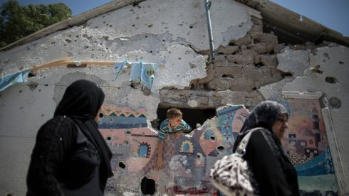 Palestinians pass by shrapnel impacts to a wall of a United Nations-run school that was reportedly hit by Israeli artillery shells, at the Jabaliya refugee camp in Gaza. Photograph: Wissam Nassar/The New York Times