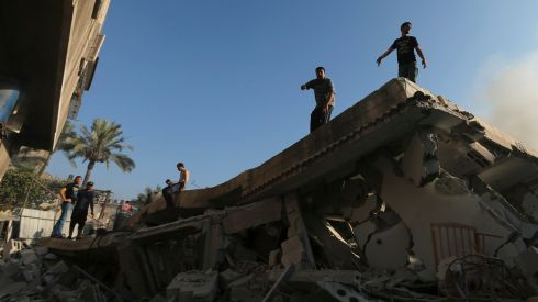 Palestinians stand atop the wreckage of a house, which witnesses said was destroyed in an Israeli air strike, in Gaza City. Photograph: Mohammed Salem/Reuters