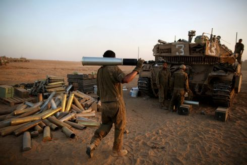Israeli soldiers carries a shell next to a Merkava tank in a staging area, close to the Gaza border, in southern Israel. Photograph: Abir Sultan/EPA