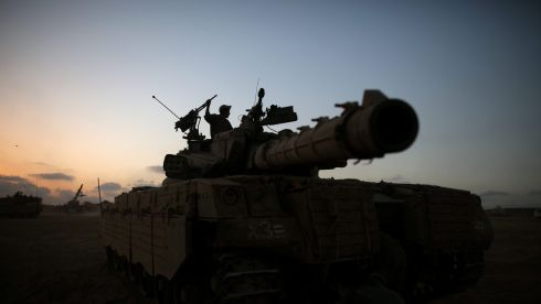 An Israeli soldier on a  Merkava tank  in a staging area, close to the Gaza border, in southern Israel. Photograph: Abir Sultan/EPA