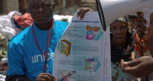A Unicef worker holds a poster bearing information about best practices to prevent the spread of the Ebola virus, in Conakry, Guinea. Photograph: Reuters