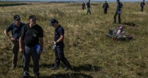 International crime scene experts from The Netherlands and Australia work at the crash site. The Ukrainian military says pro-Russian rebels are bottled up around Donetsk, allowing international investigators and recovery crews to begin work. Photograph: Mauricio Lima/The New York Times