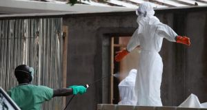 Liberian nurses in protective clothing being sprayed with disinfectant after preparing several bodies of victims of Ebola for burial in the isolation unit of the ELWA Hospital in Monrovia, Liberia. Photograph: Ahmed Jallanzo/EPA