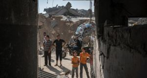 Palestinians examine damaged buildings in Gaza city. Photograph: Sergey Ponomarev/The New York Times