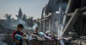 Palestinian children gather books from the rubble of the Imam Shafi'i Mosque in Gaza city. Photograph: Sergey Ponomarev/The New York Times