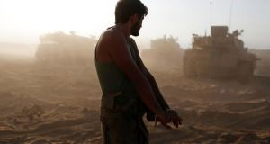 An Israeli soldier stretches at a staging area near the border with Gaza . Photograoh: Siegfried Modola/Reuters