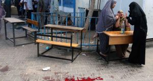 A Palestinian woman reacts as a pool of blood from wounded and dead people is seen on the ground following what witnesses said was an Israeli air strike at a United Nations-run school, where displaced Palestinians take refuge, in Rafah . Photograph: Ibraheem Abu Mustafa/Reuters