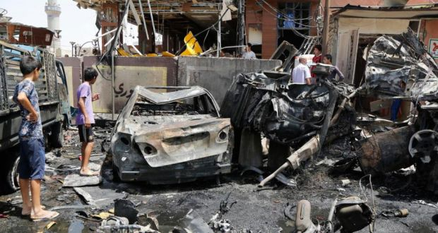 People gather at the site of a car bomb attack in Baghdad's Sadr City on Friday. Violence has killed 1,737 people, mostly civilians, in Iraq in July. Photograph:  Wissm al-Okili/Reuters